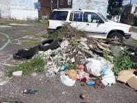 A pile of trash and parked vehicles on the former Helen Street basketball court