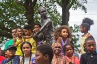 "Smith Playground Summer Camp participants, and Boys and Girls Club members cluster around the new ""MVP"" Ora Washington statue. (Kimberly Paynter/WHYY)"