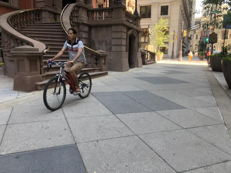 A cyclist rides along the sidewalk in front of the Union League on South Broad Street | Meir Rinde