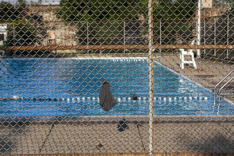 A forgotten shirt hangs on the fence at Dendy's pool after closing on a July evening. | Maggie Loesch