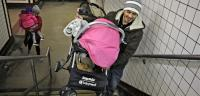 A man carries a stroller up the stairs at the 8th and Chestnut exit from the Market Frankford line. (Emma Lee/WHYY)