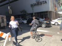 A pedestrian and a bicyclist pass on the sidewalk at 18th and Market streets | Meir Rinde