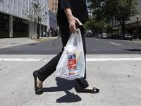 A woman walks with a plastic bag in this file photo