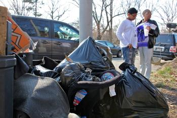 A resident of Cobbs Creek Parkway complains that the neighboring auto shop dumped trash in front of her house, for which she was fined. (Emma Lee/WHYY)