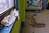 A T-shirt catches the drips from a leaking window frame in a multi-purpose room used by children at Vare Rec Center. | Emma Lee/WHYY