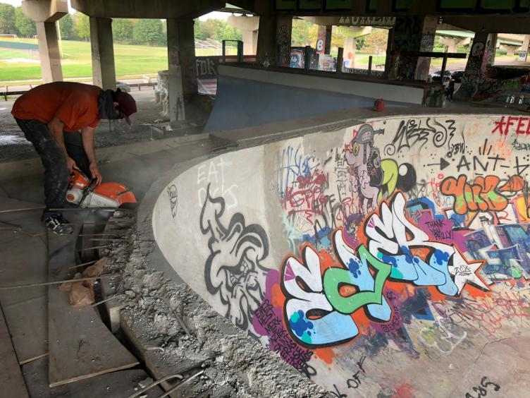 A skater cuts concrete around a bowl at the skatepark in FDR Park.