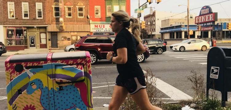 A woman runs past a pile of litter next to a Big Belly trash can on South Broad Street.