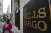 A woman walks past a Wells Fargo bank branch in view of City Hall. (AP Photo/Matt Rourke)