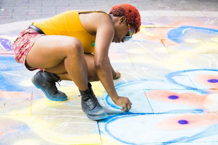 Alaina Ewins adds to a chalk mandala at Ridge Avenue and North Broad Street. The mandala was created by the Mural Arts Program in support of Philly Free Streets.