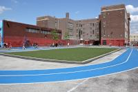An astroturf field and track direct rainwater runoff toward a containment basin in the recently rebuilt Taggart School playground in South Philadelphia. (Emma Lee/WHYY)