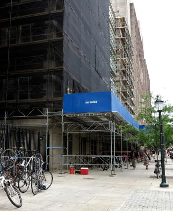An example of scaffolding wrapped in safety netting and a sidewalk shed outside of the Hospital of the University of Pennsylvania.