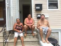 Ana Marrero, Milagros Soto, and Pablo Cuevas catching a cool breeze on the stoop of their home in Hunting Park.