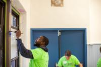 Andre Wright paints puts a new coat of paint on a window frame in the Sharswood Athletic Rec Center. (Brad Larrison for NewsWorks)