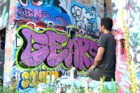 Street artist Tim Lee takes a break from spraying the walls at Graffiti Pier. Joel Wolfram/for WHYY