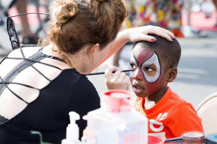 Chrissy Jones paints the face of Kadeem Gaines, 3, as Spiderman at a booth advertising The Met Philadelphia, at Broad and Poplar Streets.