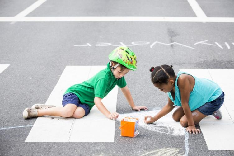 Geffen Reinherz, 5 (left), and Skyla Car, 7, draw with chalk at Broad and Poplar Streets during Philly Free Streets.
