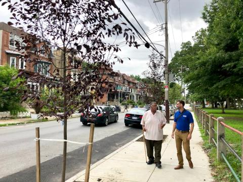 Gregorio Pac Cojulun (left), and Dan Schupsky, an outreach specialist, stroll along one of the new sidewalks.