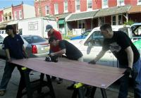 Volunteers brace plywood as it is cut for use in one of the Aspen Street homes. | Christine Fisher