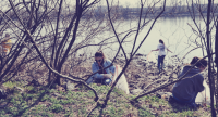 Volunteers clean up trash along the Schuylkill River at Batram's Garden. | United by Blue