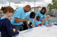 Mayor Michael Nutter (L) and Comcast's Amy Smith (R) pitch in to help a group of young Comcast Cares Day volunteers with a paint