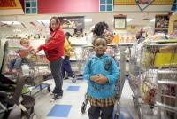Customers smile while waiting in line at the deli at Cousin's supermarket