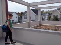 Ashby Leavell, a graduate student in University of Delaware's public horticulture program, examines the green roof deck.