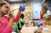 Isabel Slaughter, 8, paints a ceramic sculpture in Emily Coleman's ceramics class at Olney Rec Center. (Emma Lee/WHYY)