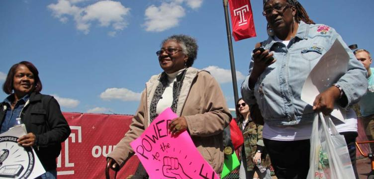 Jacqueline Wiggins (center), a long time resident of the Temple University area, joins neighbors and students in an April 2016 march against a proposed stadium. (Emma Lee/WHYY)