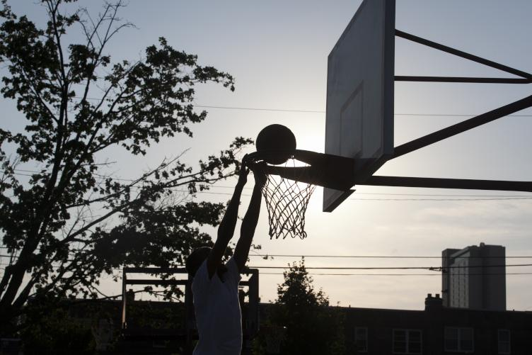 Keith Bolden dunks a basketball as the sun sets at Dendy Playground on July 10. | Maggie Loesch
