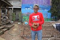 Luis Martinez holds a chicken that he has been nursing in a community garden in Kensington. (Emma Lee/WHYY)