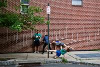 Members of the Swiss theater troupe Asphalt Piloten take to a Philadelphia street Tuesday evening for a performance of