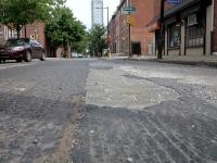 Milled road reveals trolley track and cobblestone street buried below the asphalt.