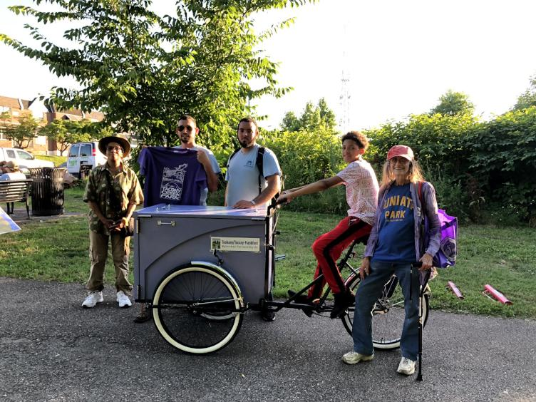 Multiple generations of friends and stewards of Tacony Creek Park, with the 'Creek Mobile.' Credit: Diana Lu/WHYY