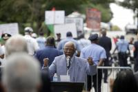 ormer Philadelphia Mayor W. Wilson Goode Sr. speaks to supporters, as protesters demonstrate in the background, during a ceremony to celebrate the naming of a street after him Friday in Philadelphia.