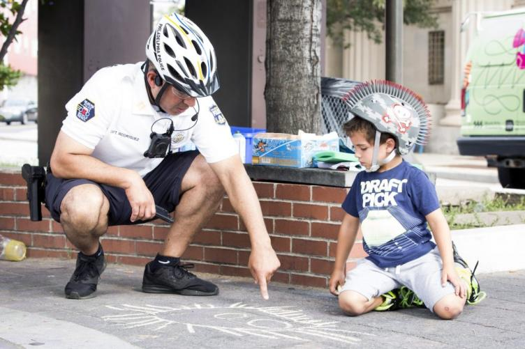 Philadelphia Police Capt. Javier Rodriguez compliments Logan Miller, 5, on a monster he has drawn with chalk at Broad Street and Ridge Avenue. during Philly Free Streets