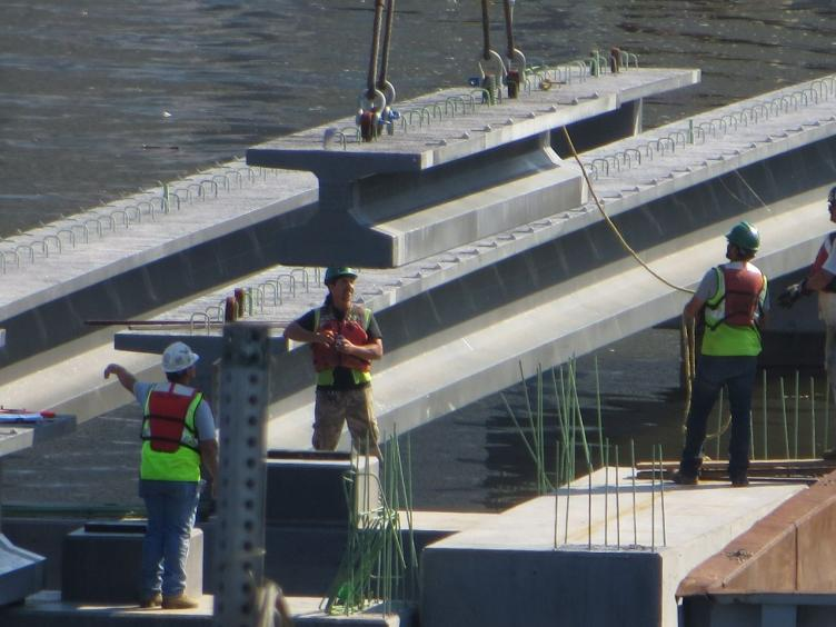 A concrete section of the boardwalk is lowered into place