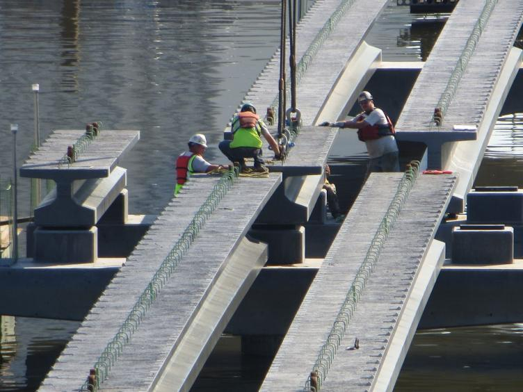 Construction workers guide a concrete portion of the boardwalk into place as a crane lowers it from above
