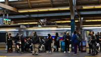 Riders wait on a SEPTA train platform for the Regional Rail to arrive. (Kimberly Paynter/WHYY)
