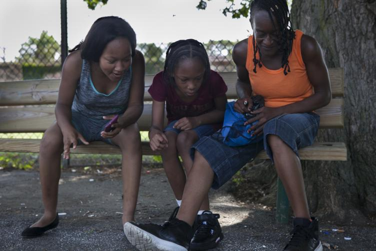 Savannaha Marion, 15, Cionne Richardson, 13, and their mother Michelle Richardson look at a caterpillar on the blacktop at Dendy on June 29. | Maggie Loesch