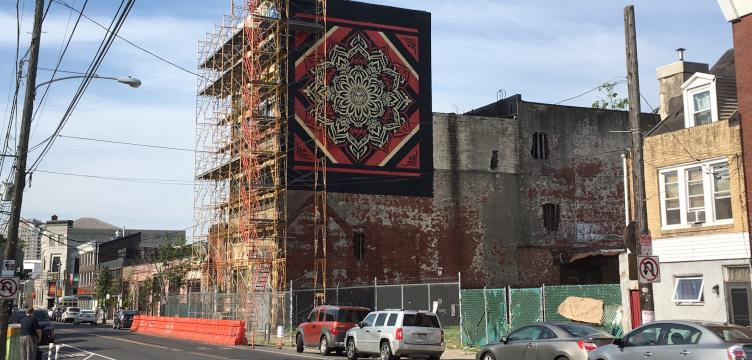Scaffolding surrounds the proposed site of a Fishtown hotel, next to Frankford Hall. The sidewalk has been blocked off for years. A Shepard Fairey mural is painted on the side of the building.