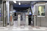 SEPTA rider passes through the turnstile at the 8th and Market station. (Emma Lee/WHYY)