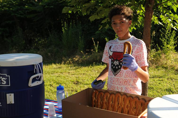 Tacony Creek Park Keeper James Megron passes out pretzels and water during the Tacony Creek block party.