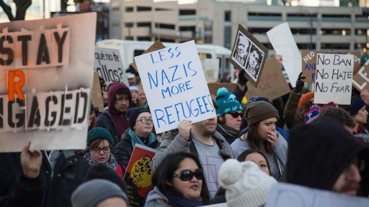 Thousands of protesters gather at Thomas Paine Plaza for a