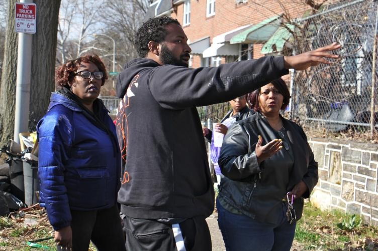Tracey Gordon (left) and residents of Cobbs Creek Parkway complain to the owner of L & K Auto Sales about parking and trash problems caused by his shop. (Emma Lee/WHYY)