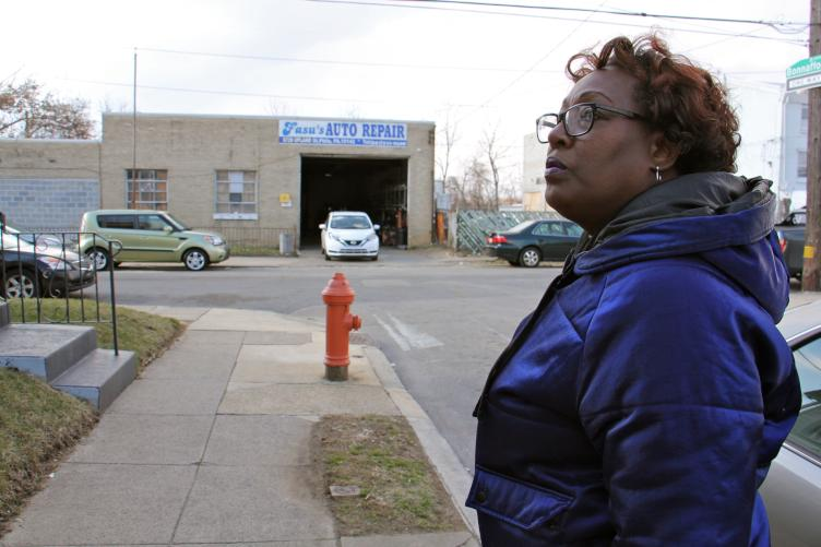 Tracey Gordon stands in a residential block of Bonnaffon Street, which is bookended by auto repair shops. (Emma Lee/WHYY)