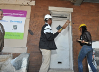 Two students knocked down the front door of 2006 Wingohocking St. to signify the start of the second sustainable rehab project