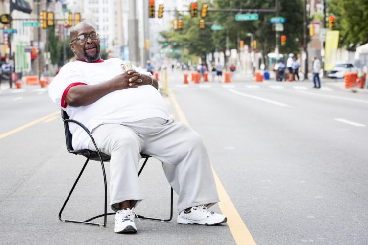 Tyrone Davis sits in a chair he brought to the center of Broad Street between Fairmount Avenue and Brown Street. He lives nearby.