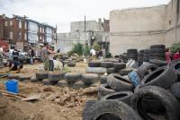 Urban earthship: At a vacant lot near Lancaster Avenue and 41st St, volunteers use hundreds of tires to build an urban earthship. | Lindsay Lazarski / WHYY