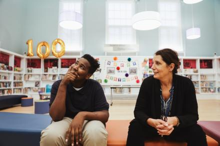 Waki Perry, 14, and Branch Manager Lynne Haase talk in Logan Library's children's room. (Neal Santos for PlanPhilly)