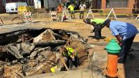 Workers examine a sinkhole in Kensington. (Bobby Allyn/WHYY)